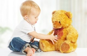 baby plays in doctor toy teddy bear and stethoscope